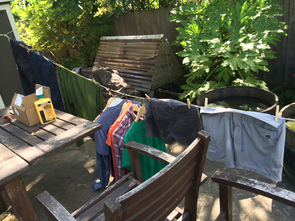 Spraying clothes with permethrin to ward off mosquitos.